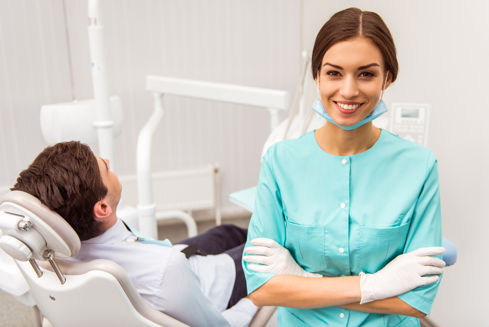 A young female dental assistant sits near a patient while smiling at camera.