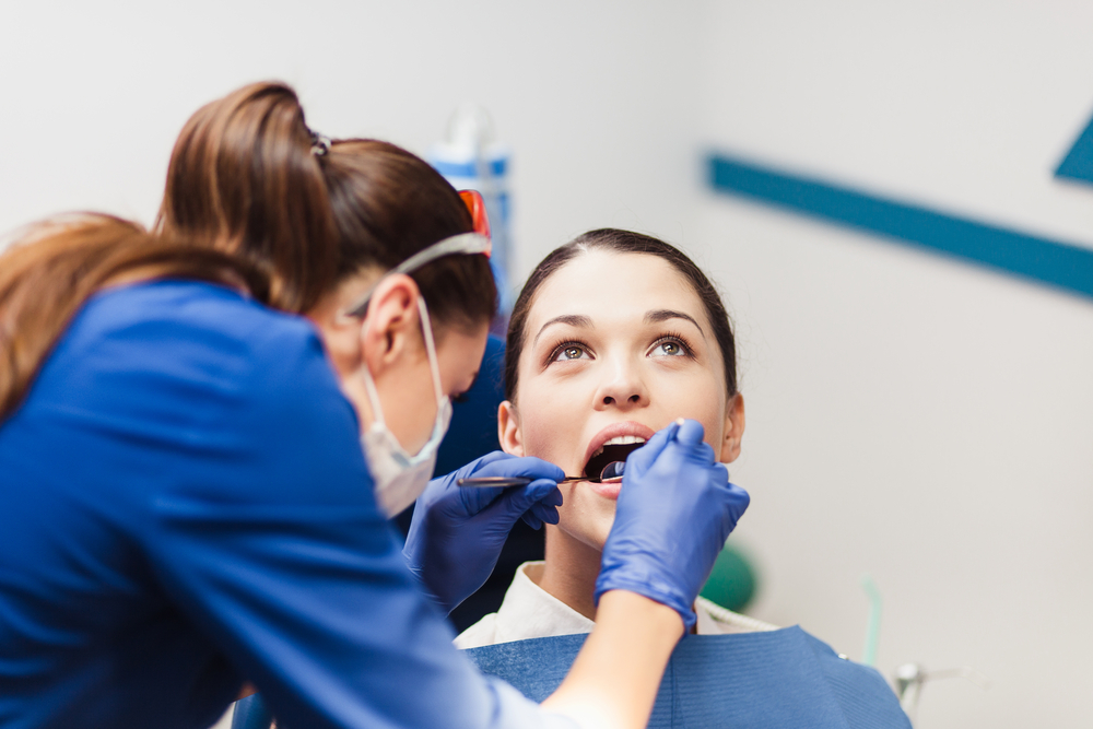 A young female dental assistant works on a female patient's teeth.