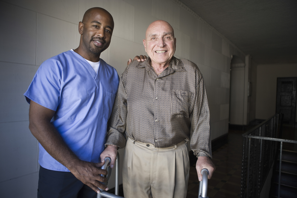 Medical assistant stands next to elderly patient