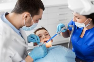 Boy getting his teeth cleaned by dentist and Dental Assistant