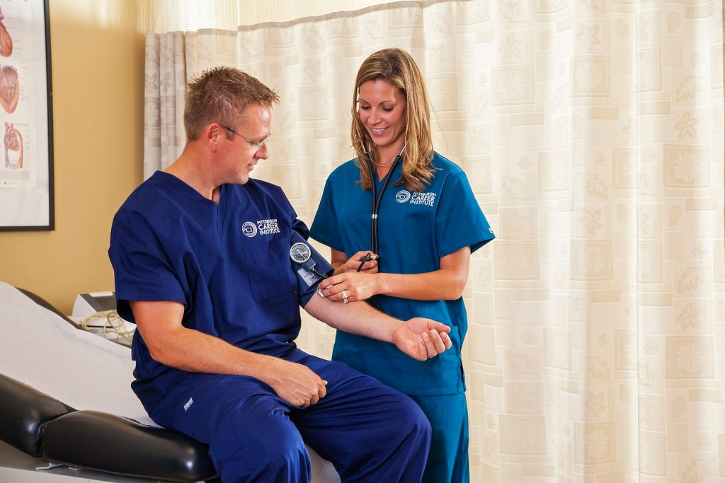 People in Pittsburgh Career Institute scrubs testing blood pressure